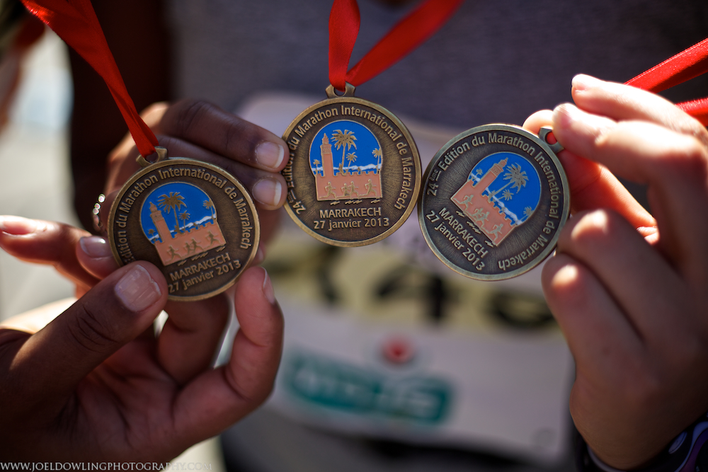 Three tough ladies holding their rewards for completing the Marrakech half marathon.