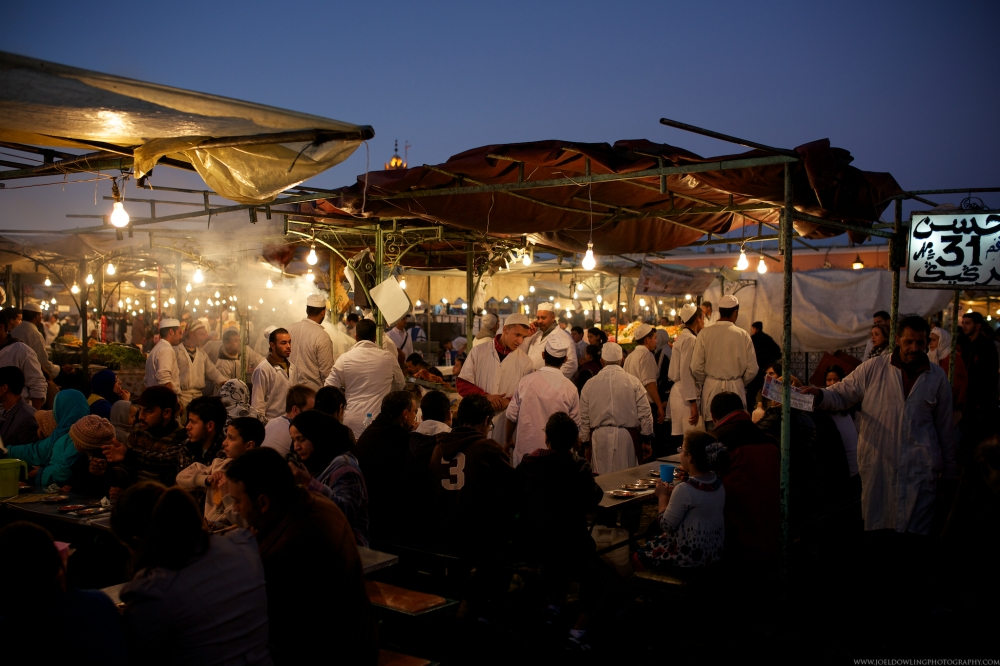 A typical night restaurant at Jemma el Fnaa.  Families eating dinner, an army of cooks and a hype man pushing his menu in front of everyone walking by.